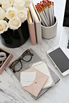 A feminine desk topped with books, glasses, and accessories that enhance the color palette.