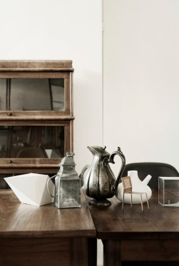 Construct a modern industrial impression by uniting a wooden table with steel and ceramic vases.