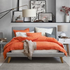 Bring the attention into the center of the bedroom with a vivid orange comforter complimented with white accents and grey walls.