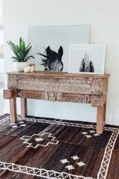 A dark brown patterned fabric carpet goes along with the wooden entryway console table.