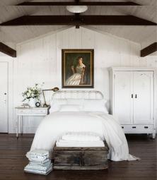 A soft white frame enhances this classical bedroom.