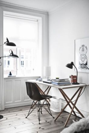 A neutral home office decorated with a single black lamp.