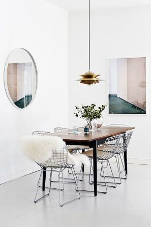 A modern dining nook with hanging lights.