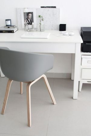 A minimalist grey chair compliments perfectly with the white desk and black belongings.