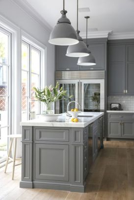 These grey hanging lights are in perfect harmony with the accent cabinets and marble counters.