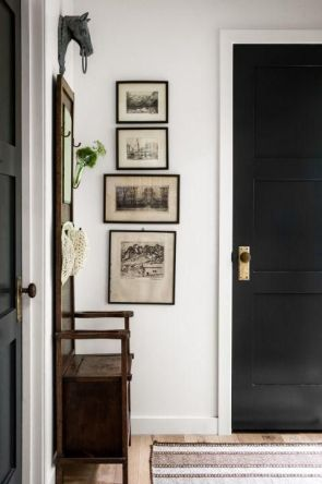 Dark colored wall art balances out the color of the door.