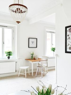 A simple white home with a small dining table and stool.