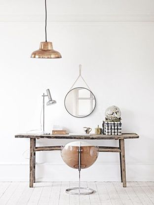 An industrial chair with copper hanging lamp.