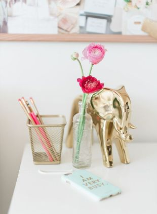 A golden elephant arranged next to a wire pencil basket.