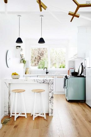Marble counters paired with a set of white stools.