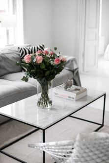 A vase of pink roses with the marble coffee table creates a feminine feel.